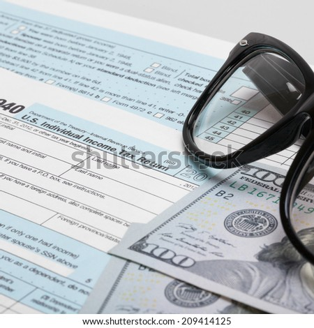 USA 1040 Tax Form with glasses and two 100 US dollar bills - 1 to 1 ratio - stock photo