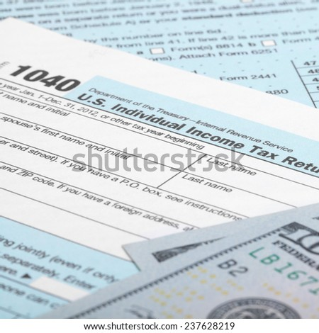 USA 1040 Tax Form with 100 US dollar bills - taxing concept - stock photo