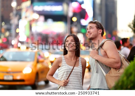 USA travel - Times Square couple tourism in New York City NYC. Young tourists visiting famous Times Square in the Big Apple in Manhattan, USA, at night by yellow cabs and busy streets. - stock photo
