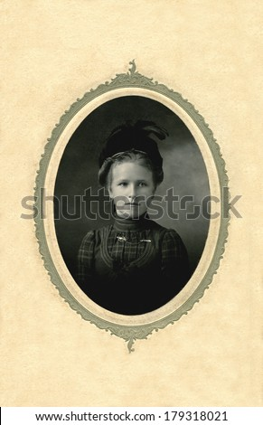 USA - WISCONSIN - CIRCA 1885 A vintage cabinet card portrait of a young girl dressed in a Victorian style dress with a Victorian style hat and feathers. Photo is from the Victorian era. CIRCA 1885 - stock photo