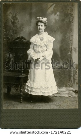 USA - WISCONSIN - CIRCA 1895 A vintage photo of a young woman. She is standing next to a chair. She is dressed in white holding a book. A photo from Victorian Era. CIRCA 1895 - stock photo