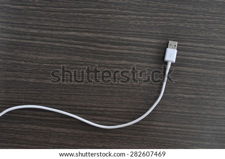 USB Cable Charging on wood table - stock photo