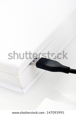 USB cable connected to a book isolated on white background - stock photo