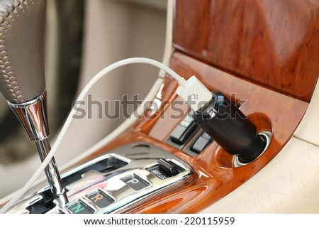 USB charger plug with charging cable on a car - stock photo