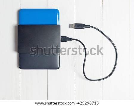 USB External Hard disk tacked on wooden background - stock photo