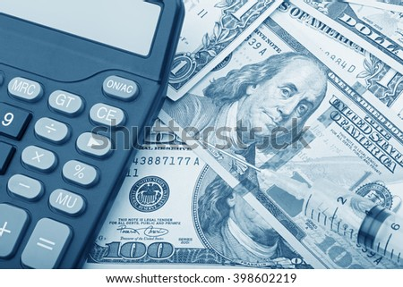 USD bank notes with a syringe and calculator showing the high cost of health care - stock photo