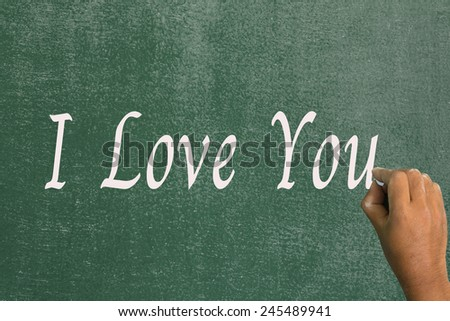 Use chalk to write the word i love you on the board. - stock photo