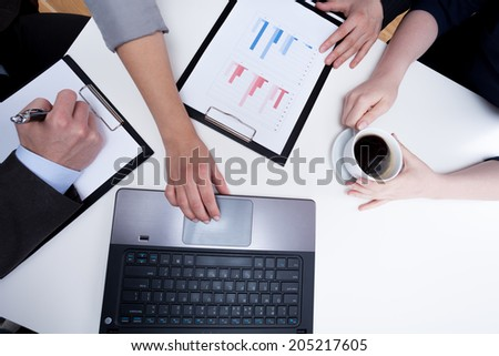 Use computer to present data on business meeting - stock photo