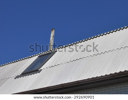 Use of asbestos in buildings is bad for health. Blue sky over the dangerous asbestos new roof tiles with roof window, skylights.  - stock photo