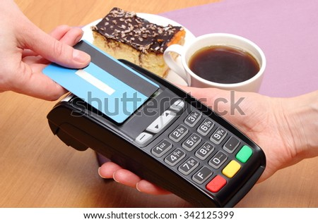 Use payment terminal with contactless credit card with NFC technology for paying in cafe or restaurant, cheesecake and coffee, finance concept - stock photo