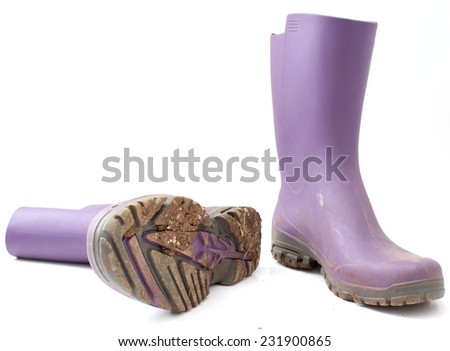 Used and dirty purple rain boots. - stock photo