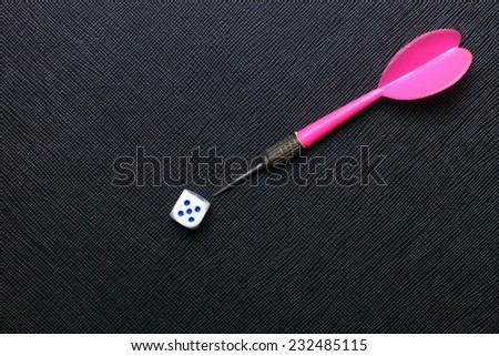 Used and vintage dartboard arrow with dice in the scene put on the black color leather surface as a background represent the entertainment game related with fortune. - stock photo
