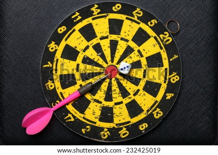 Used and vintage dartboard with arrow and dice in the scene appear a lot of damaged hole from arrow marked put on the black color leather surface as a background represent the entertainment game. - stock photo