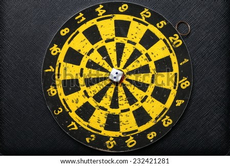 Used and vintage dartboard with dice in the scene appear a lot of damaged hole from arrow marked put on the black color leather surface as a background represent the entertainment game. - stock photo