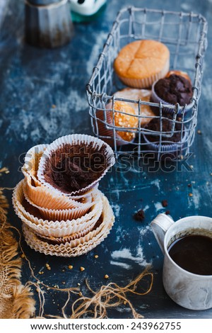 Used baking cup liners from chocolate and yogurt cakes. Food blue background. - stock photo