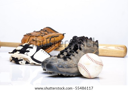 Used baseball cleats against a glove, softball, bat, and batting gloves on a white background - stock photo
