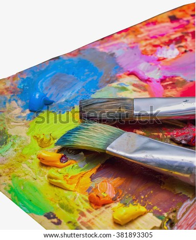 Used brushes on an artist's palette of colorful oil paint for drawing and painting - stock photo
