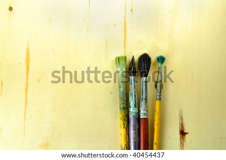 used brushes, wooden surface - stock photo