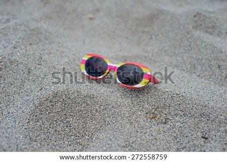 Used children's striped sunglasses on the sand - stock photo