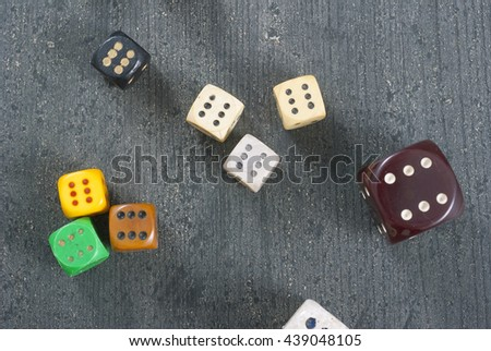 used dices with six dots on aged wooden background