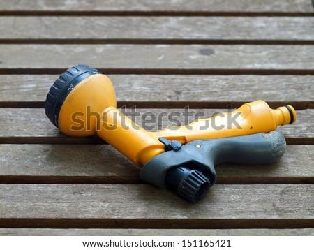 used dirty yellow garden spray gun on a wooden table - stock photo