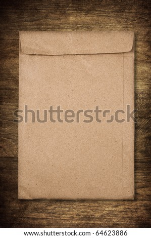 used envelope on wooden background for recycle concept - stock photo