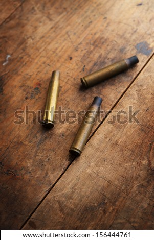 Used fire arm bullet cartridges on a old wooden floor. - stock photo