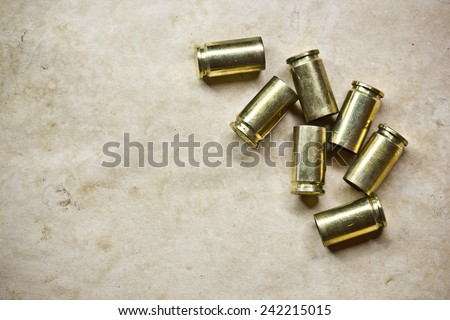 Used Glock 17 bullets shells on stained retro paper texture - stock photo