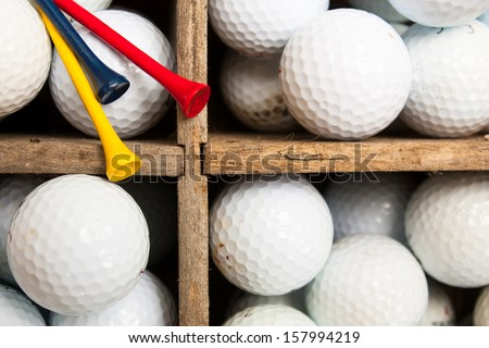 Used golf balls and colored wooden tees in a weathered antique wooden divider crate, ready for practice at the driving range.