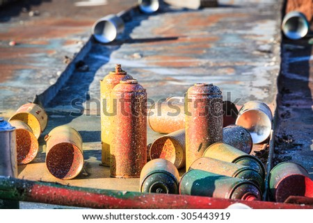 Used graffiti spray cans laying around - stock photo