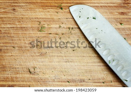 Used knife on rustic kitchen table with copy space - stock photo