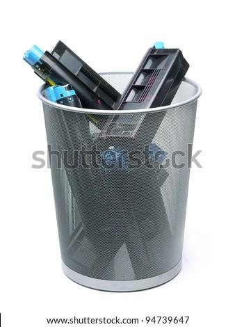 Used laser printer cartridges in metal trash bin over white - stock photo