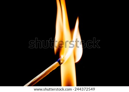 Used match and flame with black background