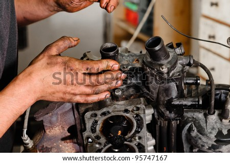 Used motor block with the hands of a worker