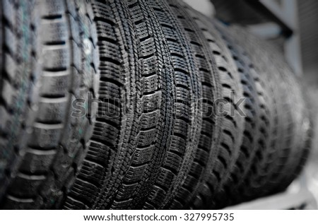 Used old car tires on the shelf at warehouse - stock photo