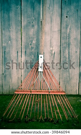 Used old flexible fork rake propped against a weathered gray wooden fence - stock photo
