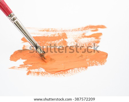 Used paint brush with orange stain on white background