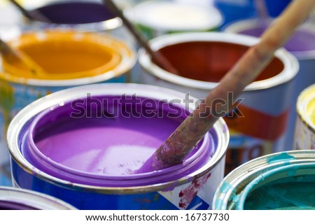 used paint buckets with various colors and painting brush - stock photo