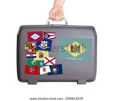 Used plastic suitcase with stains and scratches, stickers of US States, Delaware - stock photo