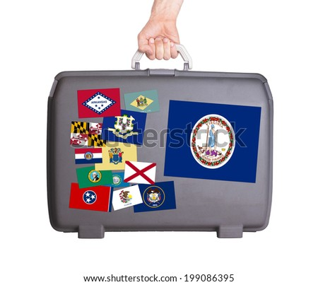 Used plastic suitcase with stains and scratches, stickers of US States, Virginia - stock photo