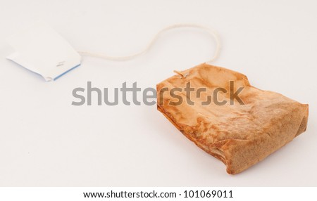 Used Tea Bag that's either Reusable or Trash on White Background - stock photo