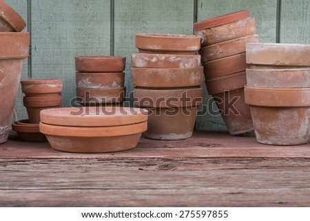 Used terracotta flower pots rest on a gardener's rough wood bench. - stock photo