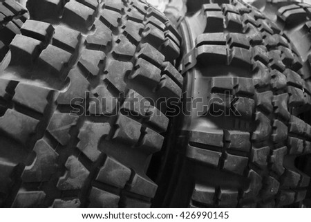 Used tires dark background. off-road. new car protector. Close up of black car rubber. big jungle tire background.