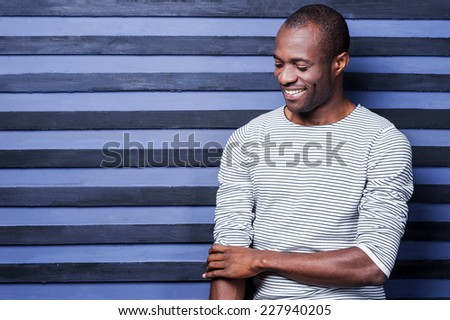 Used to look perfect. Happy young African man adjusting his sleeve and smiling while standing against striped background - stock photo