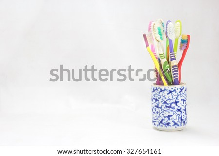 used toothbrush in cup on background - stock photo