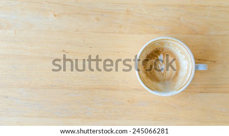 Used up coffee in while cup on wood table