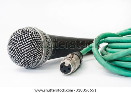 Used vocal microphone with old green xlr cable on the white background. - stock photo