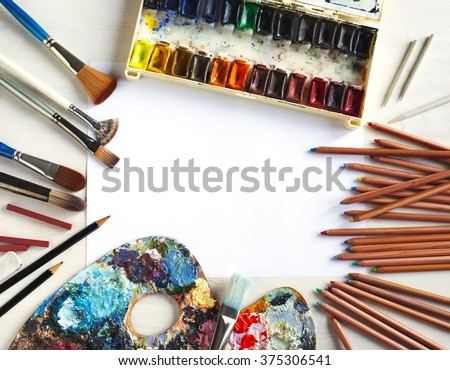 Used water-color paint-box, paint brush, pencils and pastels on wooden background with paper for copy space - stock photo