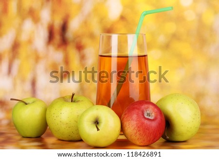 Useful apple juice with apples around on autumn background - stock photo
