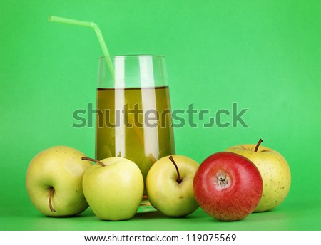 Useful apple juice with apples around on green background